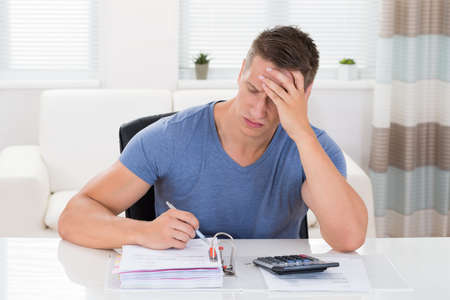 calculating: Young Stressed Man Calculating Finance At Desk Stock Photo