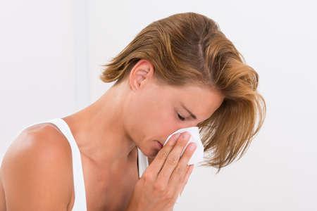 nariz: Retrato de la mujer joven que sopla la nariz en papel de seda