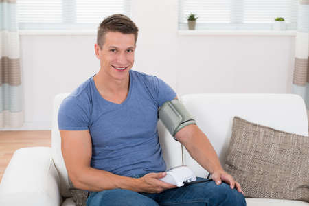 self exam: Young Happy Man Sitting On Sofa Checking Blood Pressure
