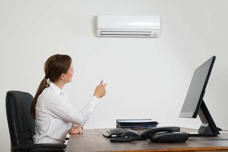 Jonge Zakenvrouw Met behulp van de afstandsbediening Voor Air Conditioner opgezet op muur Stockfoto