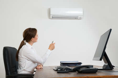 office attire: Young Businesswoman Using Remote Control In Front Of Air Conditioner Mounted On Wall