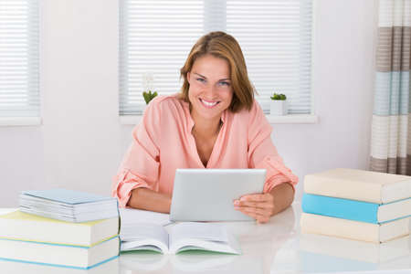 elearning: Young Woman With Books Using Digital Tablet At Desk Stock Photo