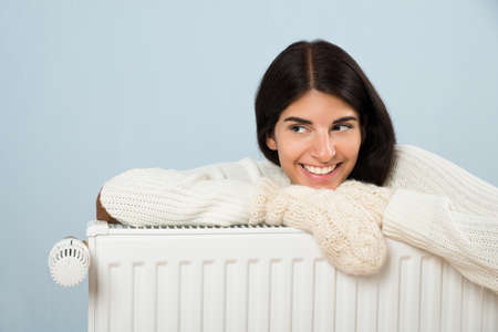 comfort: Young Happy Woman In Sweater Leaning On Radiator