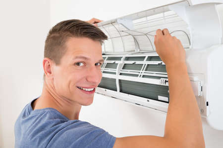 humidifier: Young Happy Man Cleaning Air Conditioning System At Home Stock Photo