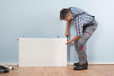 fontanero: Retrato de mediados de los adultos varones Fontanero fijación del radiador Con La Llave