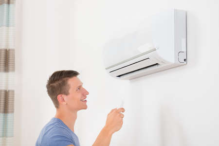 man in air: Portrait Of Happy Man Using Remote Control To Operate Air Conditioner