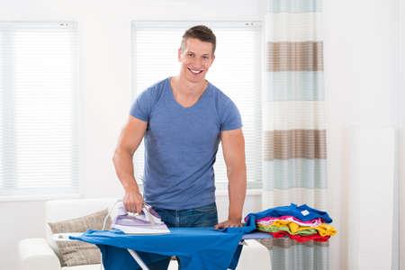 calor: Joven Hombre Feliz ropa para planchar tabla de planchar