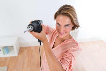taladro: Retrato de la mujer joven feliz que sostiene la máquina del taladro