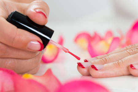 Close-up Of Female Hands Applying Red Nail Varnish Stock Photo