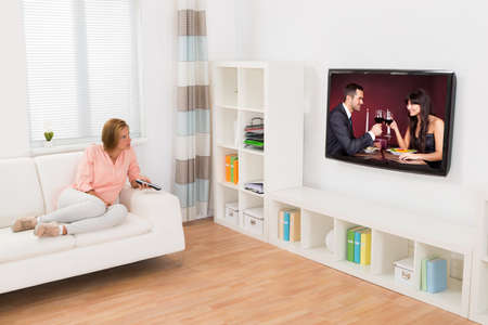 Young Woman Watching Movie On Television In Living Room photo