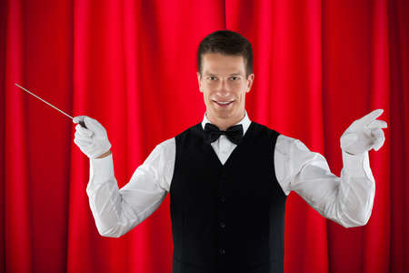 one man: Male Orchestra Conductor Holding Baton Over Red Curtain