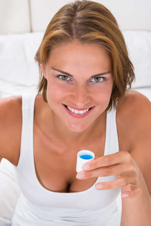 mouthwash: Retrato de la cápsula Mujer Feliz Joven Holding con enjuague bucal Foto de archivo