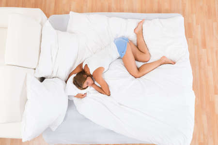 high angle: High Angle View Of Young Woman Lying In White Bed