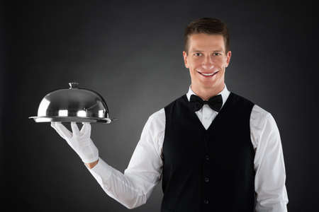 hospitality staff: Portrait Of Happy Waiter Holding Stainless Steel Cloche Over Tray