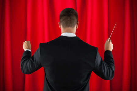 Rear View Of Male Orchestra Conductor Directing With His Baton