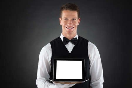 hospitality staff: Young Butler Holding Tray With Blank Display Digital Tablet