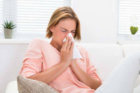 enfermos: Retrato de la mujer joven que estornuda en papel de seda