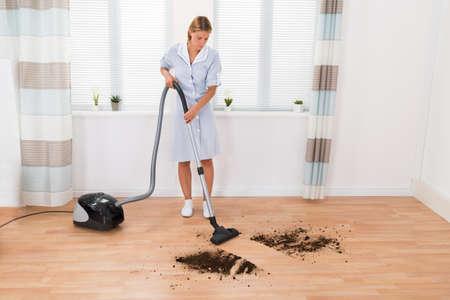 ama de llaves: Mujer joven ama de casa de limpieza de la suciedad en suelo con la aspiradora