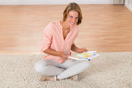 happy woman: Young Happy Woman With Diary Sitting On Carpet