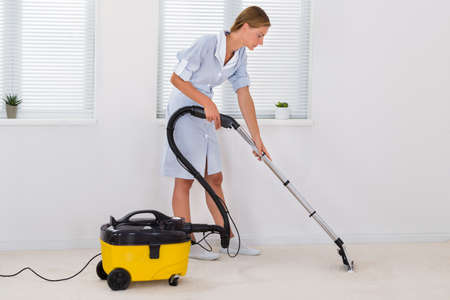 mujer limpiando: Planta de limpieza Mujer joven mucama Con Aspiradora