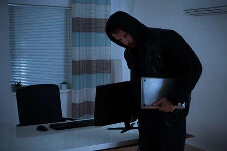 delito: Ladrón que roba la computadora y el ordenador De Oficina