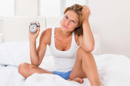 mujer enojada: Joven Enojado Mujer Sentada En La Cama Con Alarm Clock