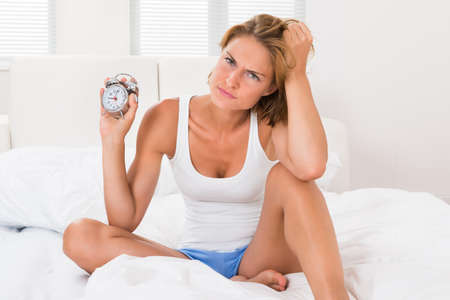 oversleep: Young Angry Woman Sitting On Bed With Alarm Clock