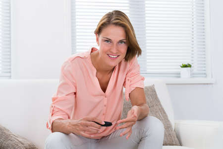 glucometer: Young Woman Sitting On Sofa Checking Blood Sugar Level With Glucometer