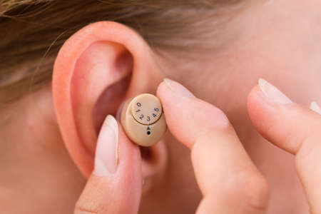 inserting: Close-up Of Female Hands Putting Hearing Aid In Ear