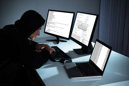 computer hacker: Male Hacker Using Computers To Steal Data In Office