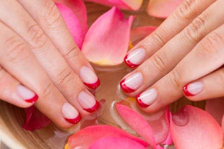 nailart: Close-up Of Woman Hands With Nail Varnish In Bowl Of Water And Petals