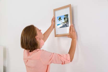 白い壁にフォト フレームを置く若い女性 写真素材