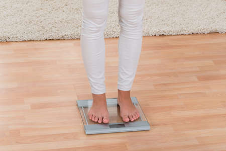 low scale: Low Section Of Woman Standing On Weighing Scale