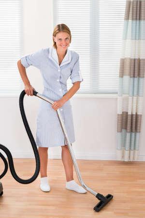 servicio domestico: Hermoso piso de madera Mujer criada de limpieza con aspiradora Foto de archivo