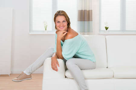 sofa furniture: Portrait Of Young Happy Woman Sitting On Sofa Stock Photo