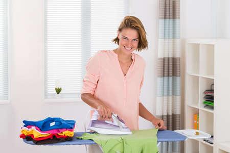 lavadora con ropa: Mujer joven planchado de ropa a bordo de planchado