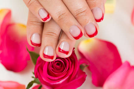 nailart: Close-up Of Hands With Manicured Nail Varnish Placed On Red Roses Stock Photo