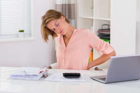 personas de espalda: Mujer joven que sufre de dolor de espalda mientras que el cálculo de impuestos en el escritorio Foto de archivo