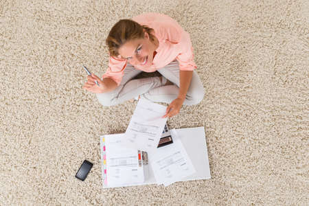 doing: High Angle View Of Young Woman Doing Calculation At Home