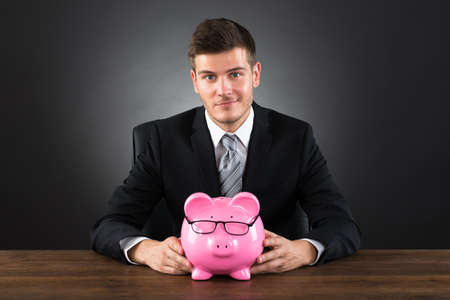 accounts: Portrait Of Young Businessman With Piggybank At Desk