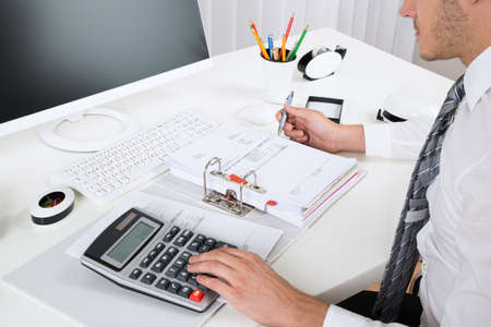staplers: Close-up Of Businessperson Calculating Budget With Calculator At Desk