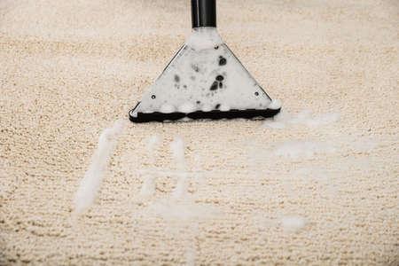 カーペットの上の泡と掃除機のクローズ アップ 写真素材