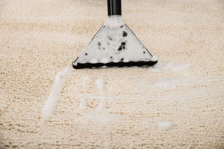 household objects equipment: Close-up Of Vacuum Cleaner With Foam Over Carpet Stock Photo