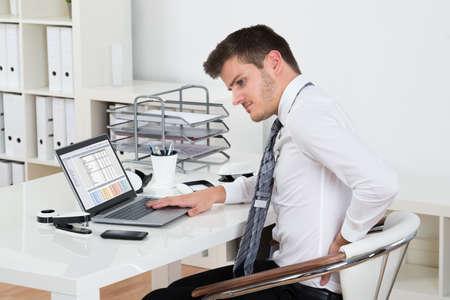 personas de espalda: El hombre de negocios joven que sufre de Backpain mientras se trabaja en la computadora port�til en la oficina