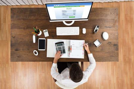impuestos: Vista de ángulo alto del hombre de negocios joven Impuesto Calculando con el ordenador en el escritorio