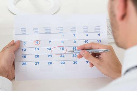 カレンダー上の日付をマーキングのビジネスマンの手のクローズ アップ 写真素材