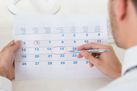 Close-up Of Businessman Hands Marking Date On Calendar