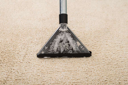 carpet: High Angle View Of Electric Vacuum Cleaner Over Carpet With Foam