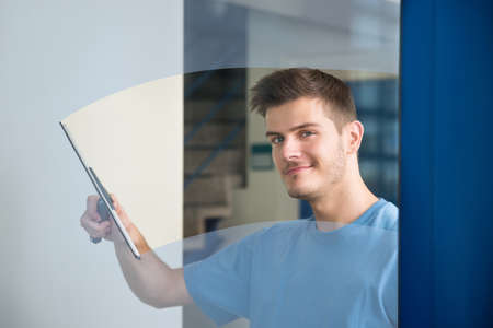 Young Male Worker Cleaning Glass With Squeegee