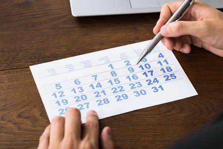 months: Close-up Of Businessperson Holding Pen Over Calendar At Desk